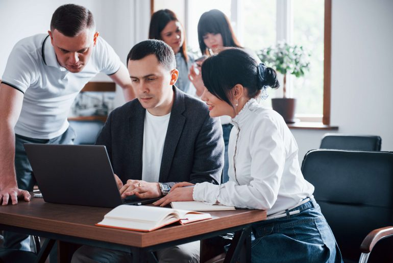 Employés autour de leur chef en train de regarder quelles assurances professionnelles obligatoires souscrire